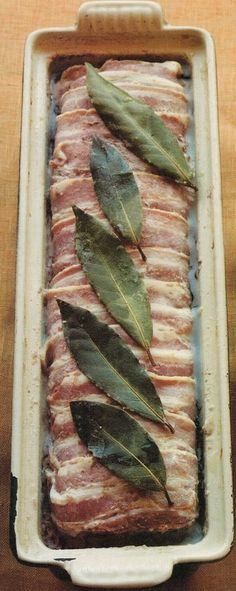 forma de cerâmica com um bolo de carne coberto com laminas de bacon e folhas de louro