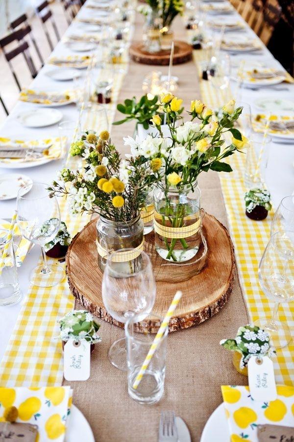mesa longa em madeira clara com toalha branca rústica quadriculada de amarelo claro e no centro arranjos improvisados de flores do campo amarelas em vasinhos improvisados de vidro reciclado