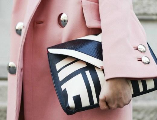 Foto em close de uma mulher segurando uma bolsa em formato carteira. A carteira colada ao corpo é preta e branca com desenho geométrico e faz contraste com o casaco em rosa bem claro ao fundo da foto usado pela mulher