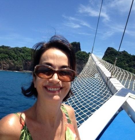 Claudia Matarazzo, usando óculos escuros , grandes, está junto a proa de um veleiro que navega pelo mar de Fernando de Noronha, num dia límpido de muito sol.