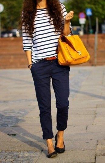 Modelo veste calças de sarja azul marinho com camiseta branca marinheira listrada de azul marinho . Nas mãos uma bolsa grande core de mostarda dá um toque de cor.