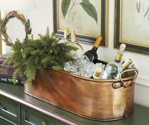 Um recipiente oval de bronze está sobre m balcão verde . Dentro estão muitas pedras de gelo e garrafas de vinho branco com um arranjo de folhas de pinho verdes dando a impressão de frescor.