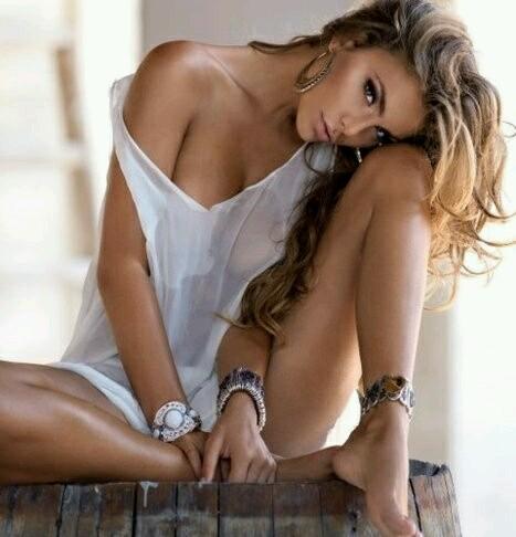 Mulher loira e jove de cabelos compridos está sentada em pose sensual com um joelho dobrado e o rosto apoiado nele usando apenas uma blusa muito fina branca e transparente que deixa ver os seios por baixo e as longas pernas desnudas