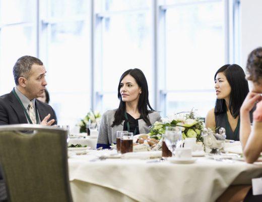 cinco pessoas almoçam num mesa redonda num restaurante, as paredes são envidraçadas, dois homens usando terno escuro, conversam com as mulheres , duas de cabelos longos, cor preta, e uma de cabelos curtos, castanhos claros. A mesa está com todos os pratos servidos.