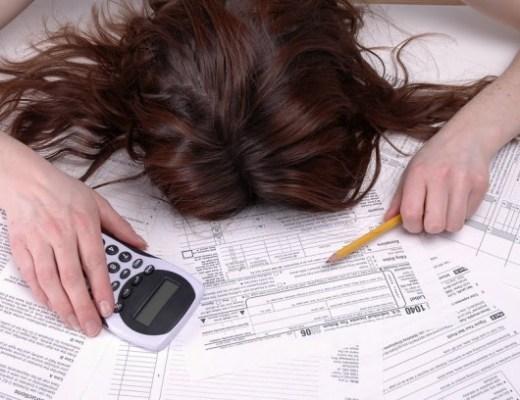 Uma moça está debruçada sobre várias contas em papel com uma calculadora na mão. Só se vê os cabelos da moça e sua postura de desespero.
