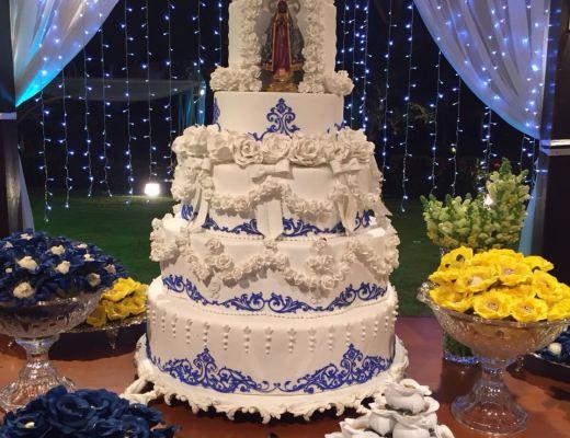 uma imagem de nossa senhora está colocada no topo de um bolo de 4 andares, branco, confeitado com pasta americana desenhada com estampa azul imitando azulejos. Ao fundo uma cortina branca complementa o visual e bem casados embrulhados em papel amarelo e branco estão em primeiro plano.