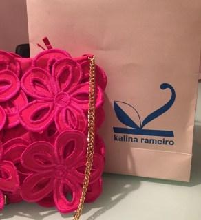 bolsa na cor lilás, em tecido com flores da mesma cor, sobrepostas, a alça é em corrente dourada. logo atrás uma sacola de papel , com os dizeres: Kalina Rameiro.