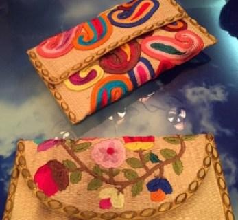 Bolsa feita de palha trançada, com apliques de flores coloridas, pintadas .