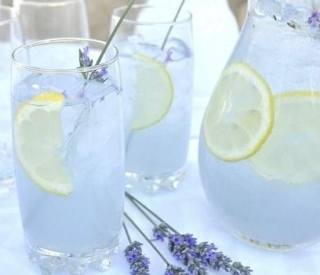 sobre uma mesa com toalha branca estão dois copos e uma jarra cheios de um refresco cor de violeta claro. Tanto a jarra quanto os copos estão enfeitados com fatias finas de limão siciliano e muito gelo. E, em cada copo tem um ramo de lavanda como se fosse um canudo.