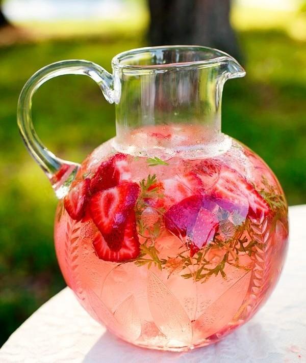 Uma jarra bem bojuda arredondada está cheia de refresco cor de rosa e através do cristal se vêem ramos de hortelã, pedaços de morangos vermelhos fatiados e muito gelo dando a impressão de cor e frescor.