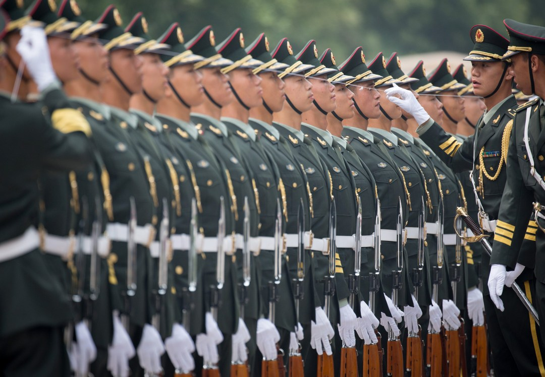Tropa Militar Chinesa em formação. todos de uniforme verde escuro. usam quepe da mesma cor. Observa-se a perfeição do alinhamento , pois eles usam uma linha, barbante que nivela o quepe na cabeça de todos eles. Um oficial comandante da tropa observa esse alinhamento.