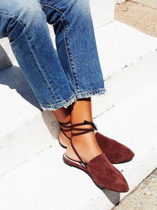 fotoa mostra apenas as pernas de uma mulher vestindo calças jeans azul claro com os pés cruzados calçando sapatos do tipo males em camurça marrom. Tiras finas prendem e enlaçam as pernas na altura do tornozelo os sapatos que são abertos na calcanhar