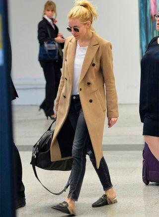 uma moça loira de óculos escuros e rabo de cavalo está vestindo uma jeans preta, camiseta branca e um mantô café com leite. Nos pés sapatos baixos tipo mules com a fivela dourada característica da grife Gucci sobre o peito do pé. A parte de trás dos sapatos é totalmente aberta deixando os calcanhares a mostra.