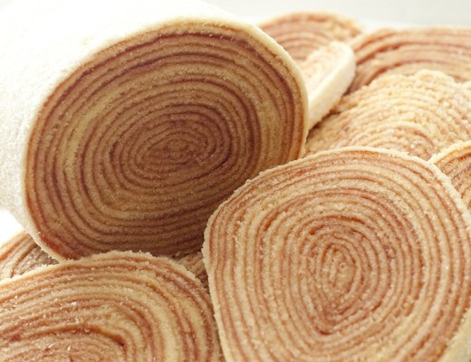 bolo de massa bem fina, enrolado em muitas camadas com recheio de goiabada e com cobertura de açúcar granulado.