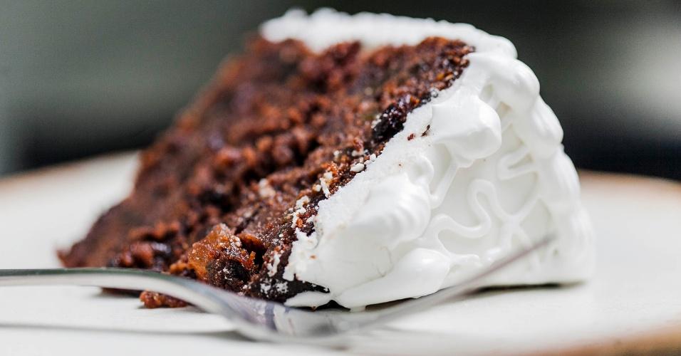 pedaço do bolo de noiva de pernambuco, onde notamos que é um bolo de massa escura com frutas e tem cobertura de clara em neve.