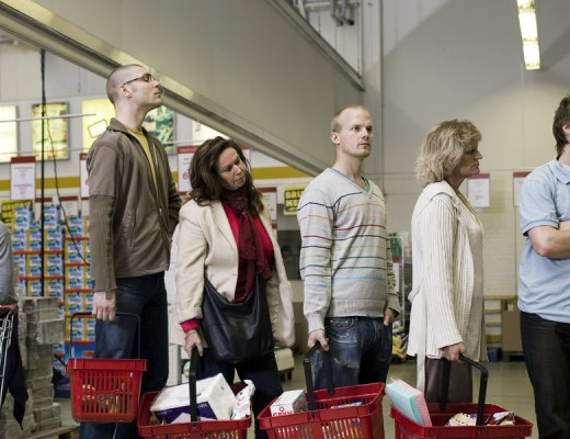 grupo de pessoas estão numa fila de supermercado aguardando para realizarem o pagamento de suas compras, todos estão segurando uma cesta com diversos produtos