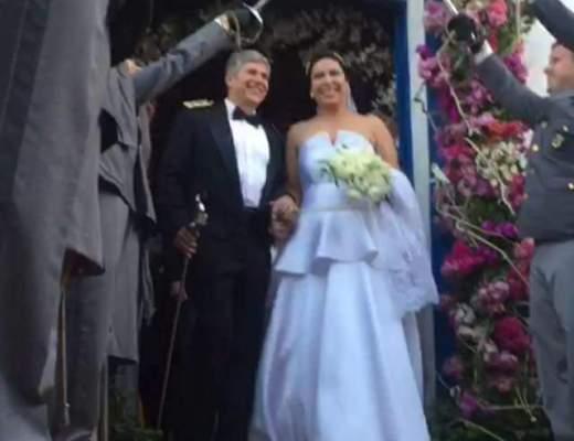 A foto mostra o casas de noivos saindo da igreja, junto a porta iniciando o trajeto sob as espadas cruzadas dos colegas do noivo todos fardados de cinza e com as espadas erguidas acima das cabeças.