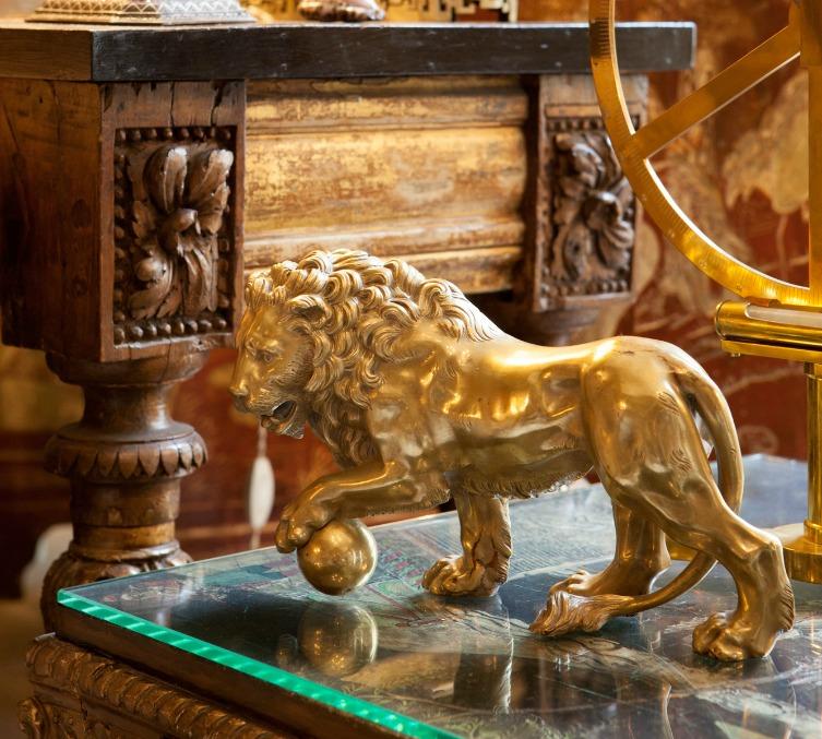 Detalhe do artesanato com a imagem de um leão, dourado, sobre uma mesa de centro com base de vidro.