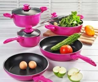 jogo d panelas esmaltado em rosa choque está sobre uma bancada branca e dentro da frigideira e da carola os legumes verdes completam com o branco o contraste colorido.