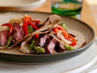 prato sobre uma mesa, contendo fajitas, carne fatiadas com pimentões, e temperos.