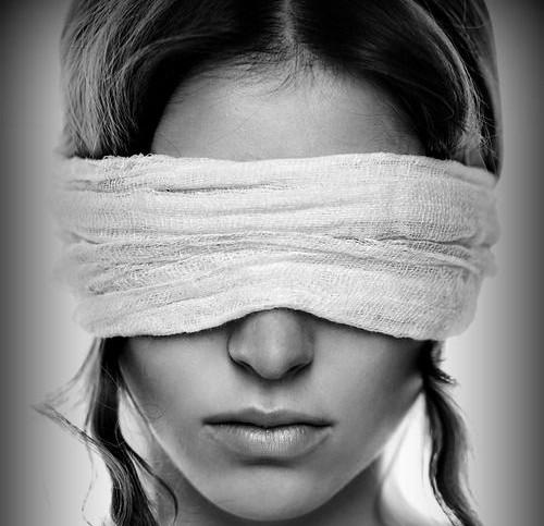 Rosto de um mulher com os olhos vendados por um pano branco. Ela tem tranças de seus cabelos nas laterais da cabeça.