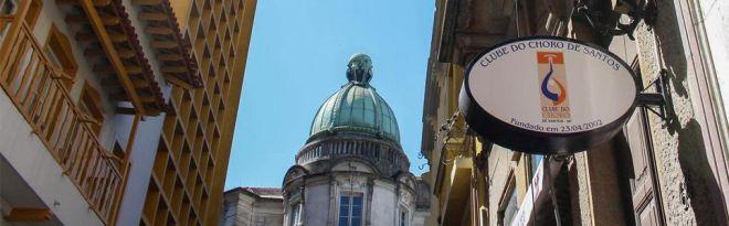 uma foto do centro histórico de Santos com uma cúpula estilo rococó mostrando ao fundo um céu bem azul.
