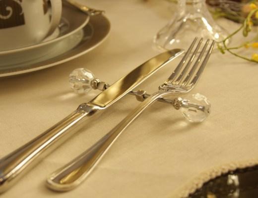 talheres em prata, garfo e faca, apoiados num descanso fino, em prata, com bordas em vidro transparente.