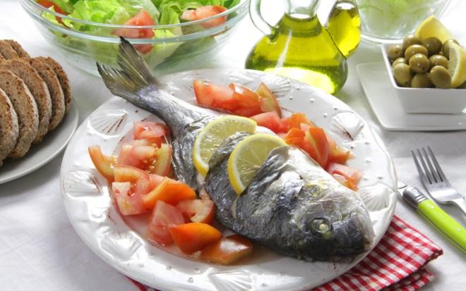 Mesa de almoço, com potes de azeite, pães, azeitonas, limões, salada de tomate e alface e ao centro um prato de porcelana branca, com um peixe inteiro, rodeado com pedaços de tomate. sobre o peixe, gomos de limão.