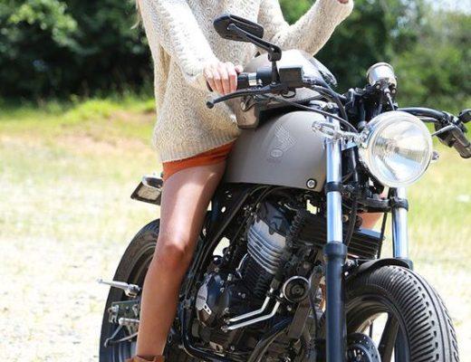 moça loira de cabelos longos está sobre uma moto vestindo um shorts marrom, uma malha branca longa e uma bota de cano curto marrom