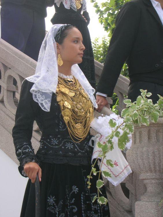 Moça de cabelos presos vestida com um vestido de mangas longas preto e véu curto branco segura ramo de flores. O cabelo castanho claro está preso e ela usa muitos colares dourados que praticamente cobrem todo o seu colo