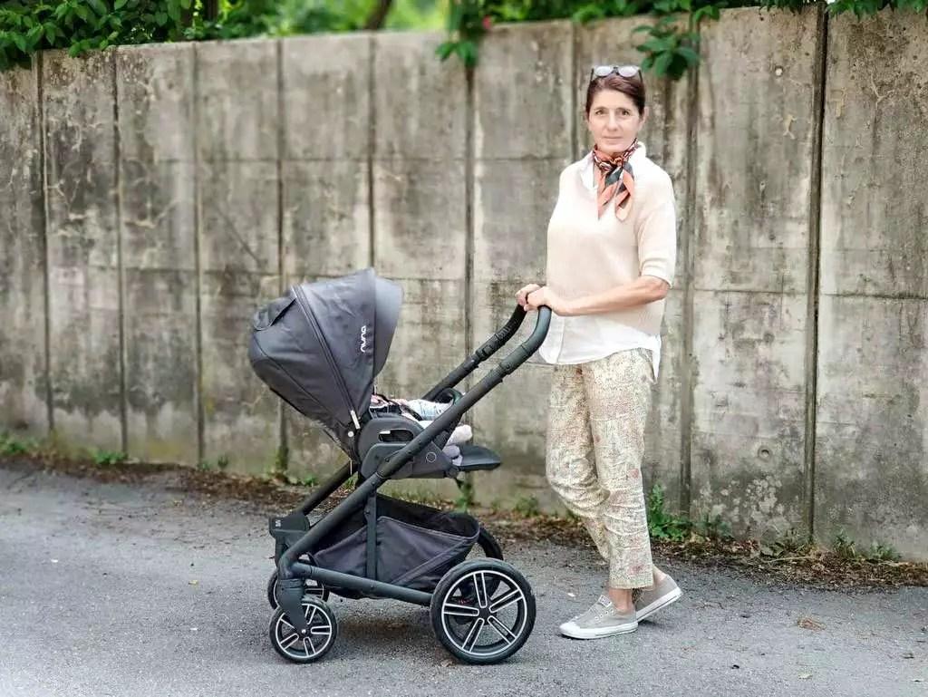 Frau schiebt einen Kinderwagen Nuna Mixx