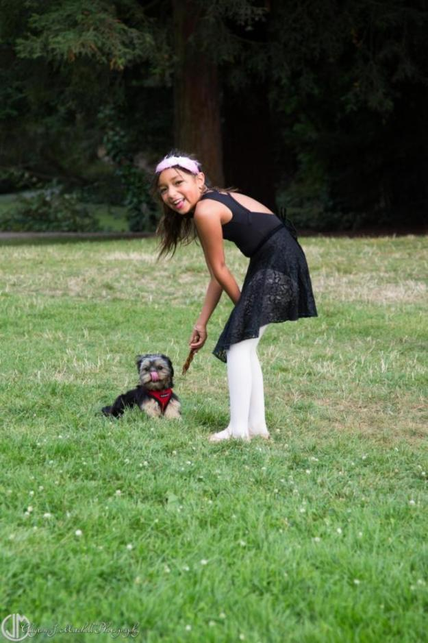girl dressed like ballerina playing with a dog