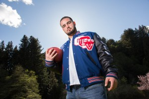 Football player with ball and letterman jacket looks down