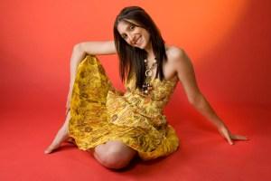 Fun studio portrait of girl sitting on orange background