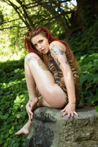 Model wearing Tiger pattern poses in woods