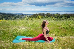 Yoga instructor doing pigeon pose in a field