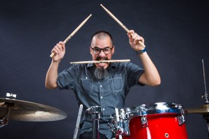 Wild drummer with drumstick in mouth