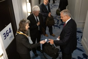 Woman passes business card at a conference