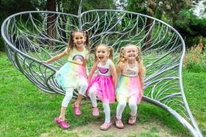 Three smiling girls in rainbow tutus