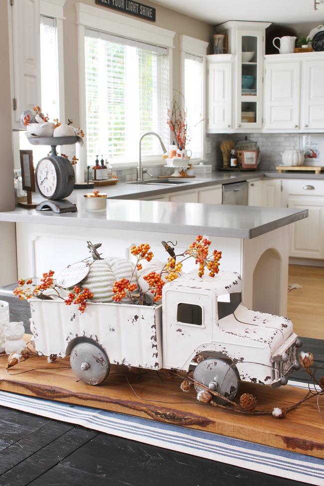 White vintage pick up truck filled with pumpkins and orange berry stems.