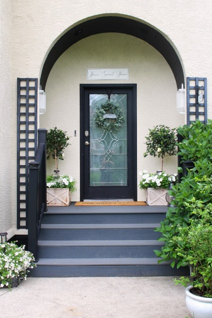 Tradtional front porch decorated for summer white magnolia topiaries and white flowers.