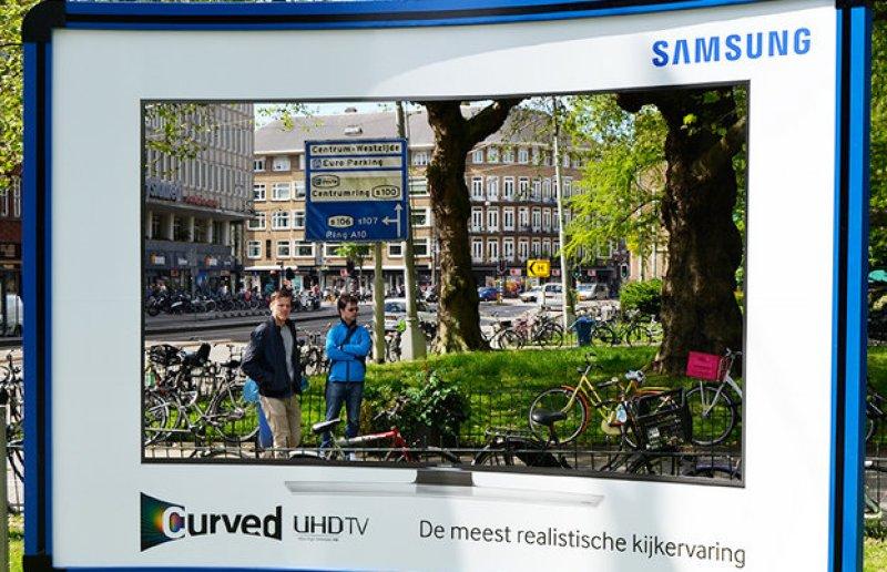 Guerrilla marketingcampagne mensen kijken door de billboard