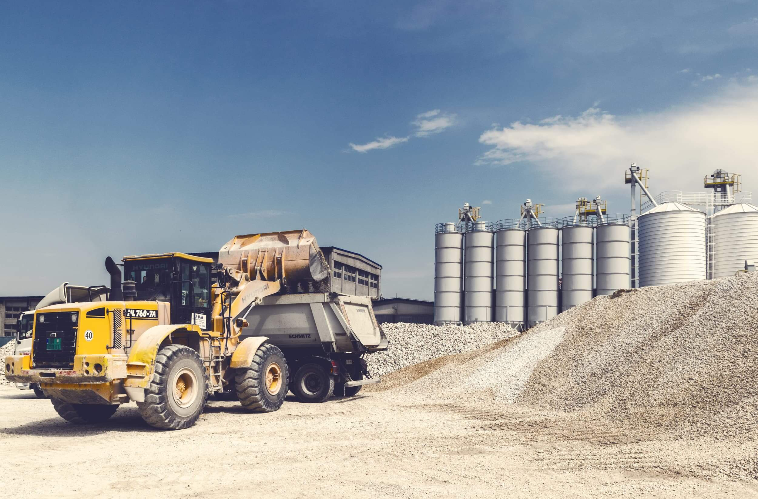 Photo of a dump truck being loaded in a gravel pit