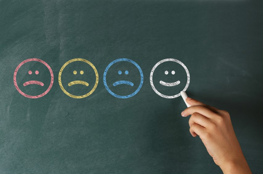Various happy and sad faces suggesting the large gap of happiness between people who are in control of their emotions or not.