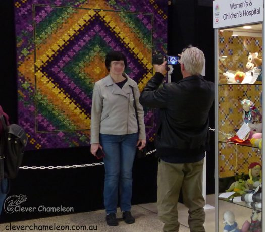 People taking a selfie with eye-catching quilt
