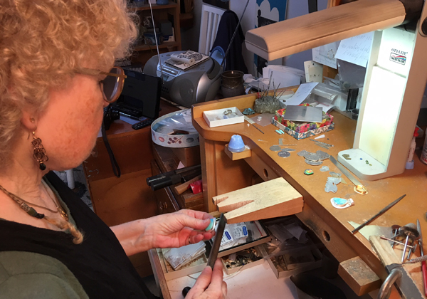 Jeweler, Marcia Dean, in her workshop creating opal rings.