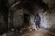 Creepy Man Stands In Deralict Brick Room With Shovel