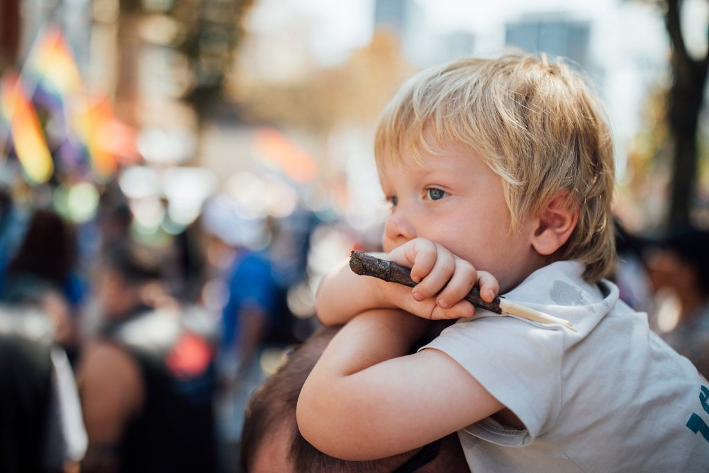 Toddler boy watching the pride parade in Vancouver Canada