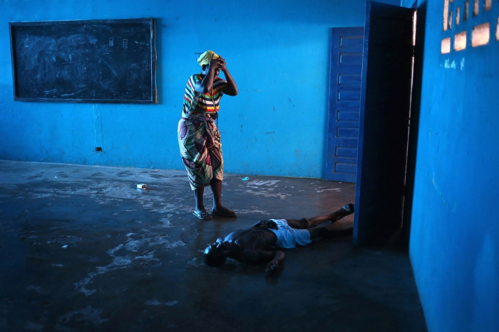 Omu Fahnbulleh stands over her husband Ibrahim after he fell and died in a classroom used for Ebola patients.