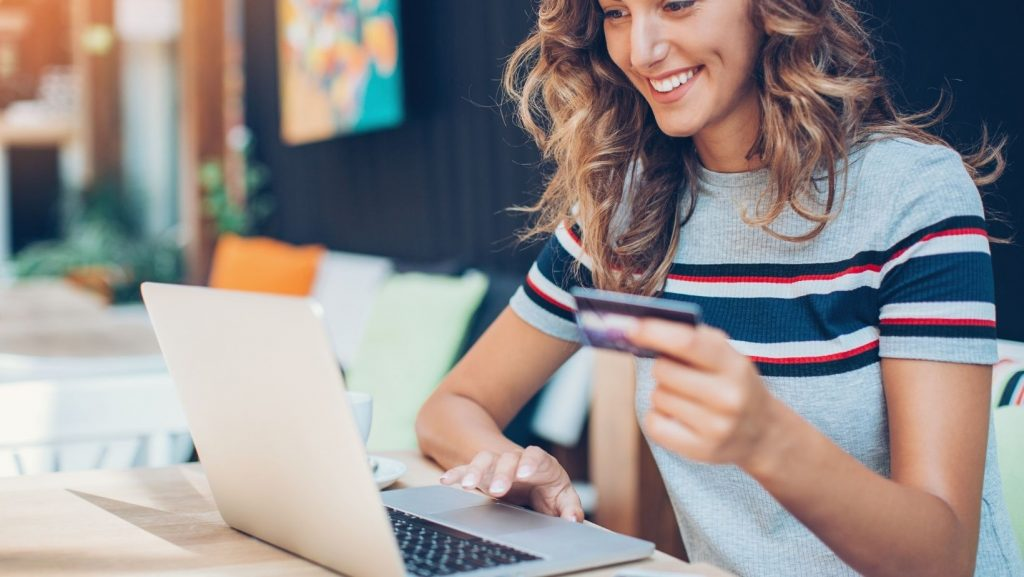 Woman smiling as she buys something online.